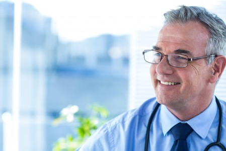 Smiling male doctor looking away in clinic