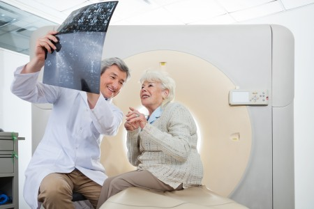 Radiologist With Patient Looking At CT Scan Results